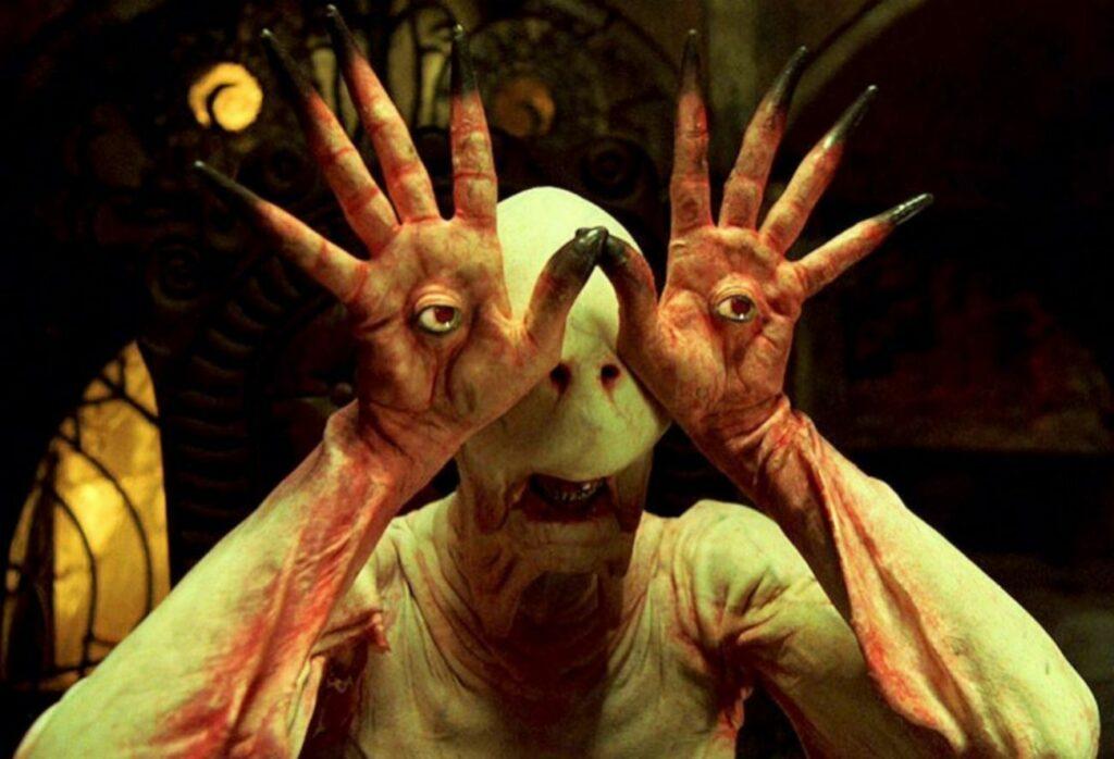 MONSTRUOS MÁS TERRORÍFICOS DEL CINE DE TERROR 2. El hombre pálido, El laberinto del fauno. Fotograma de la película de terror de monstruos laberinto del fauno. Se ve la cabeza del monstruo el hombre pálido con las manos en la cara para ver.